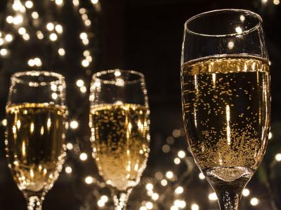 three-full-champagne-glasses-with-pretty-lights-in-the-backgroun