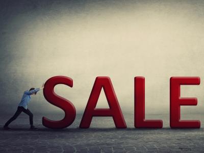 Man pushing Sale sign